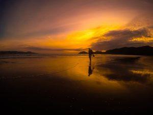 Man walking along beach at sunset.