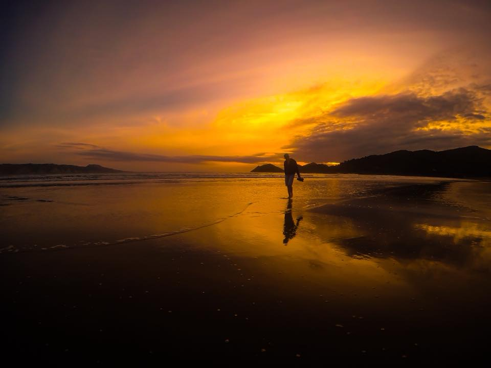 Man walking along beach at sunset.